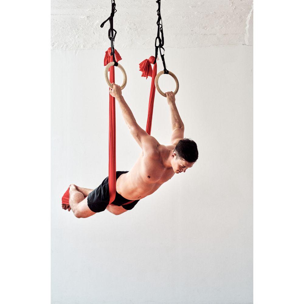 aerial-yoga-fitness-tuch-mann-im-tuch-und-an-turnringen-nach vorne-gebeugt